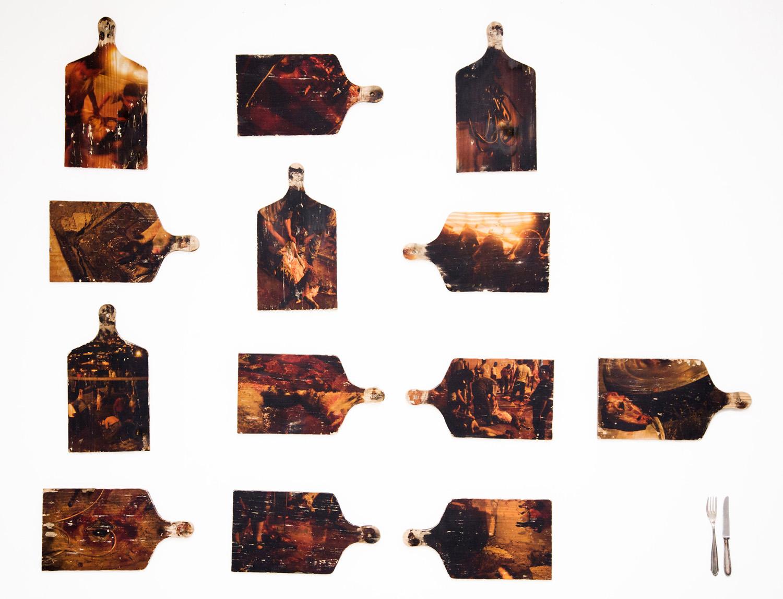 tabuas de madeira abrigam fotos de preparo de comida a partir da matança de cabras